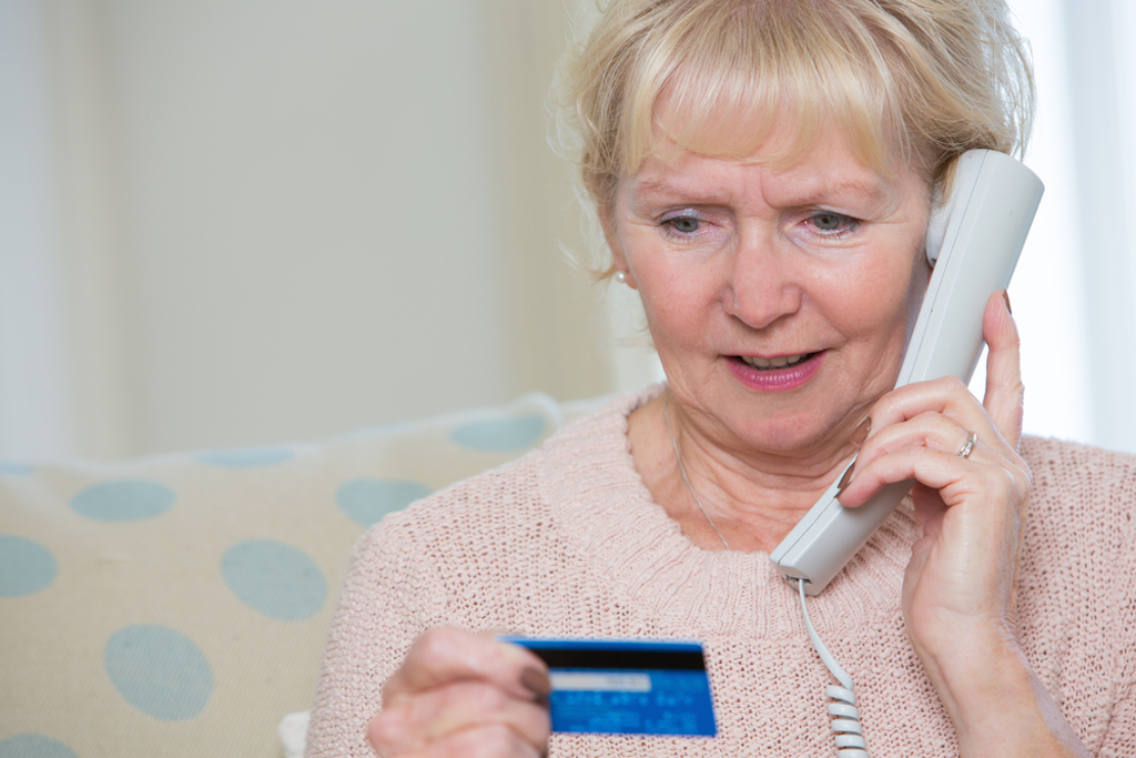 elderly woman giving credit card details by phone.