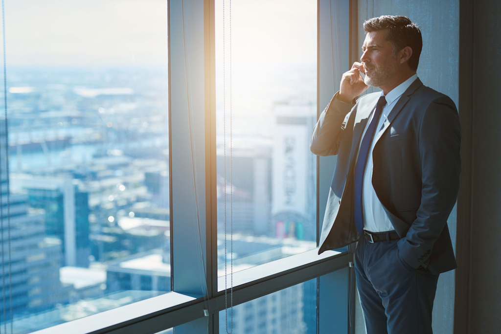CEO standing in office looking through glass window talking on phone.