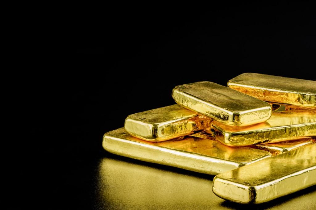 Pile of gold bars against black background