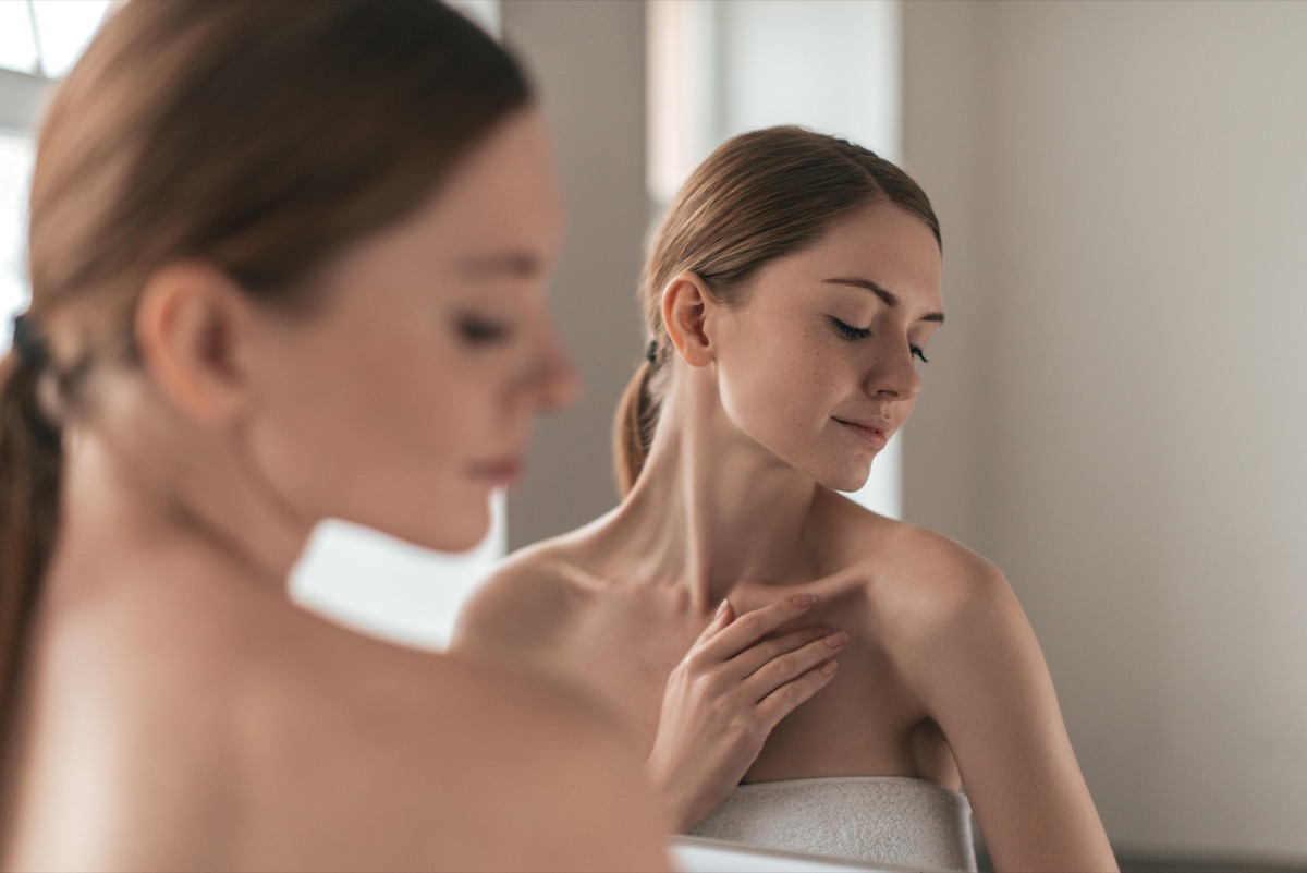 Woman looking at the skin on her shoulder