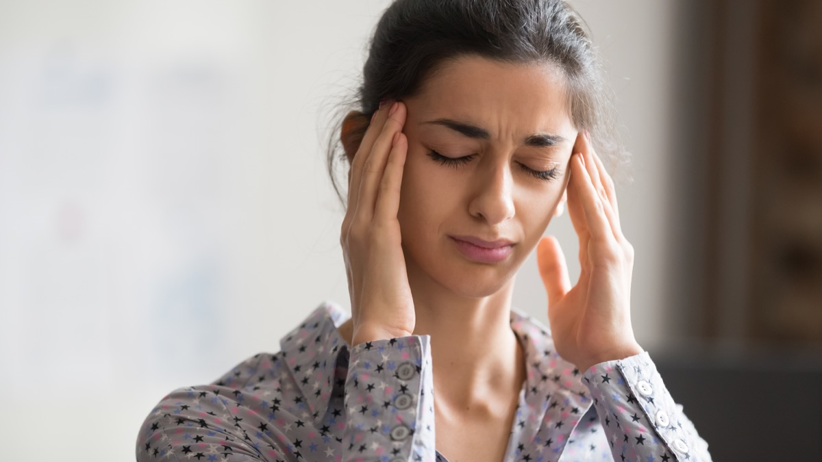 Woman rubbing her temples with headache and dizziness