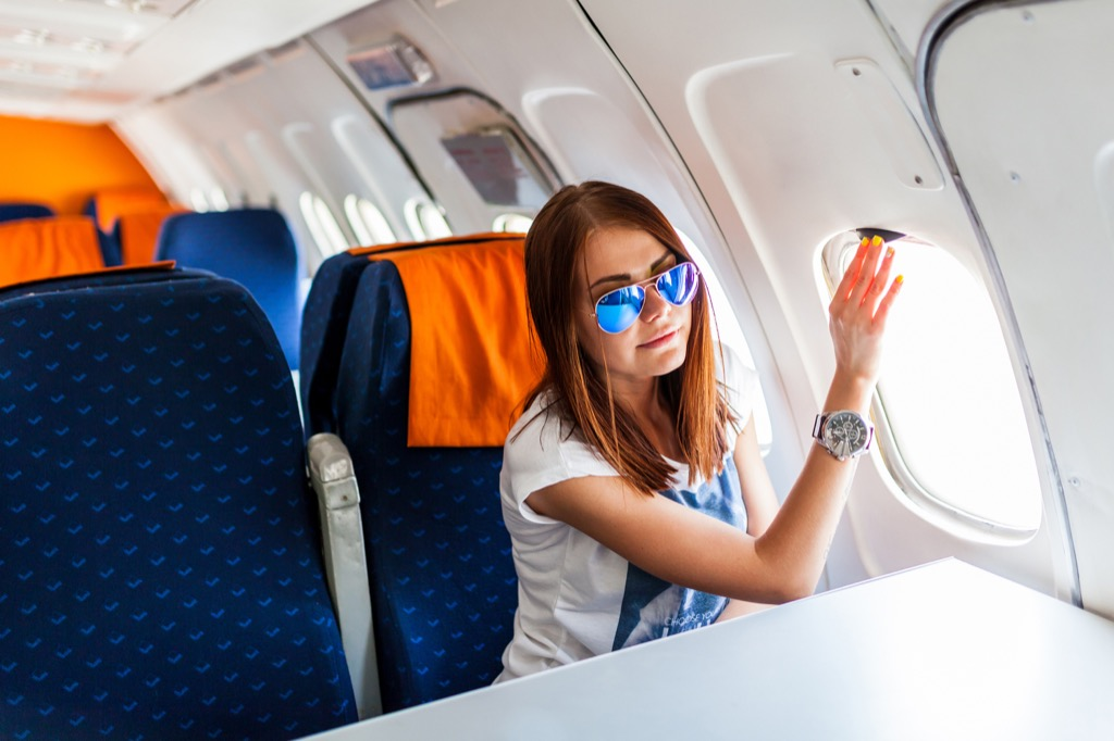 woman looking out window private plane Skin Cancer Risks