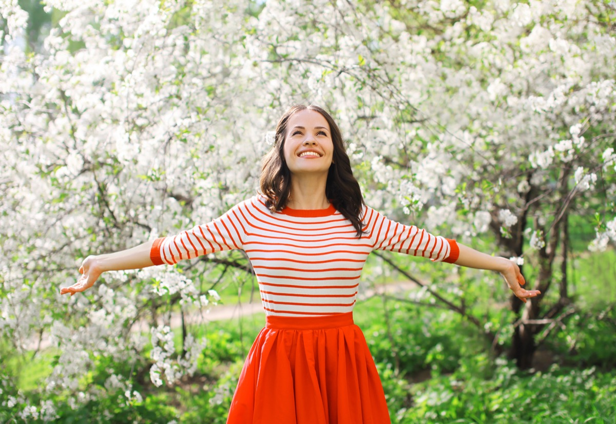 Woman outside walking through flowers and smiling