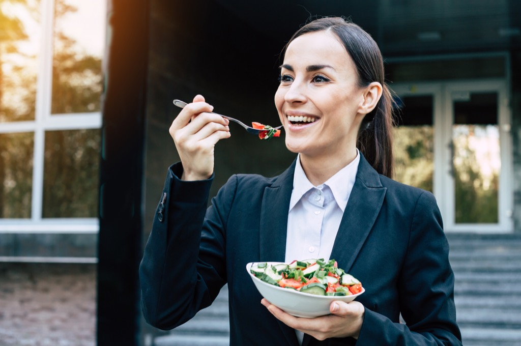 Happy woman eating salad with a fork