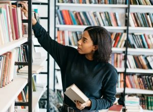 Young black woman selecting a book