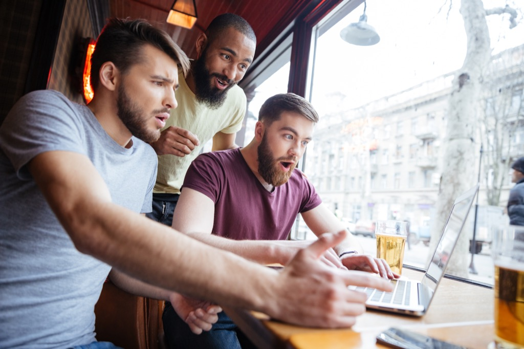 three guys look at a laptop