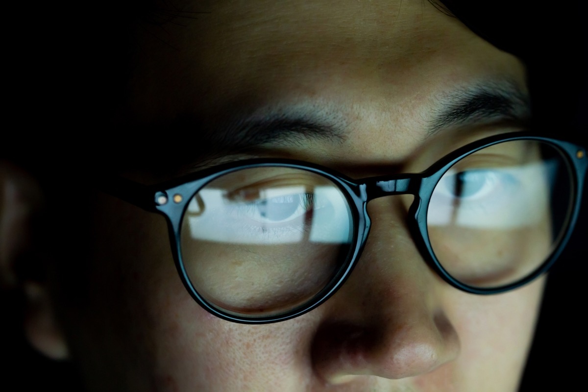Close up of Young Asian man in glasses watching videos and surfing internet on technology device in the dark (Close up of Young Asian man in glasses watching videos and surfing internet on technology device in the dark, ASCII, 109 components, 109 byte