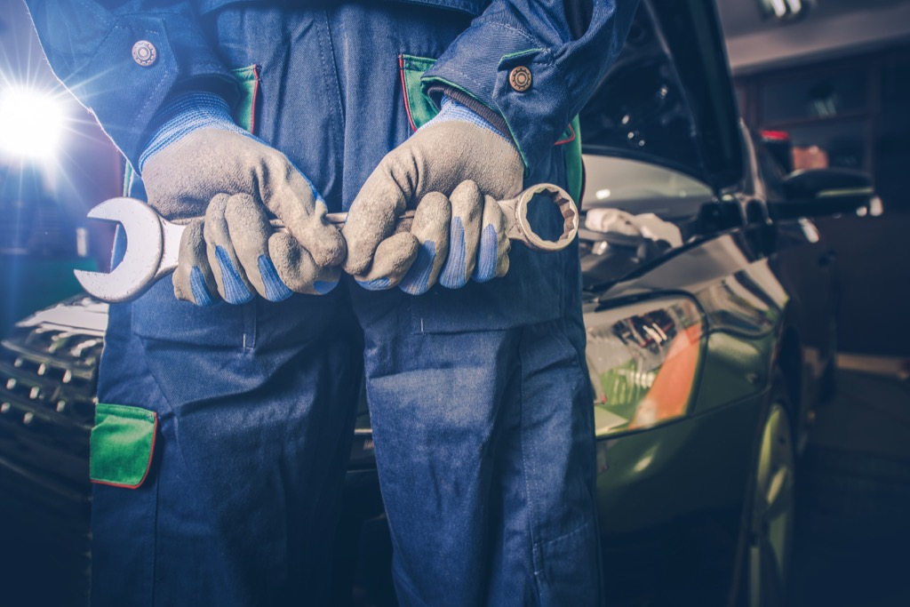 car mechanic holding wrench {stereotypes}