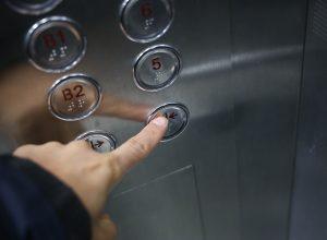 man pressing the elevator close door button