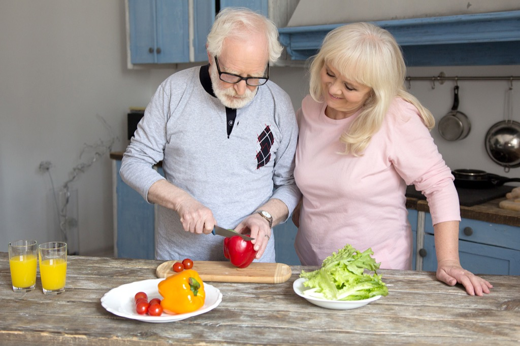 elderly couple cooking a healthy meal peppers