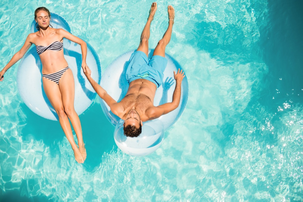 couple in pool cool off for the summer