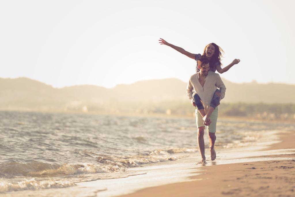couple walking on beach feeling happiness