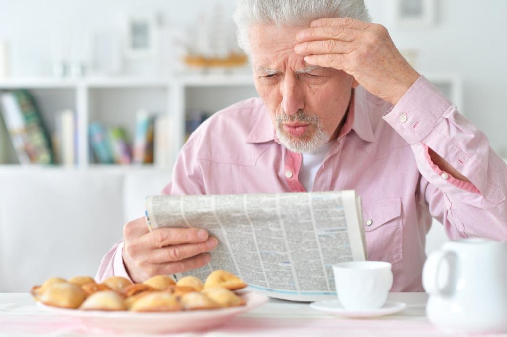 elderly man newspaper surprise shock