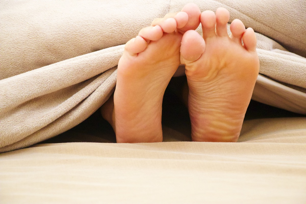 feet outside bed cover