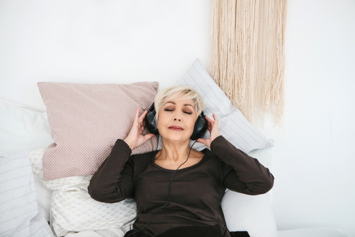 Positive elderly woman listening to music. The older generation and new technologies