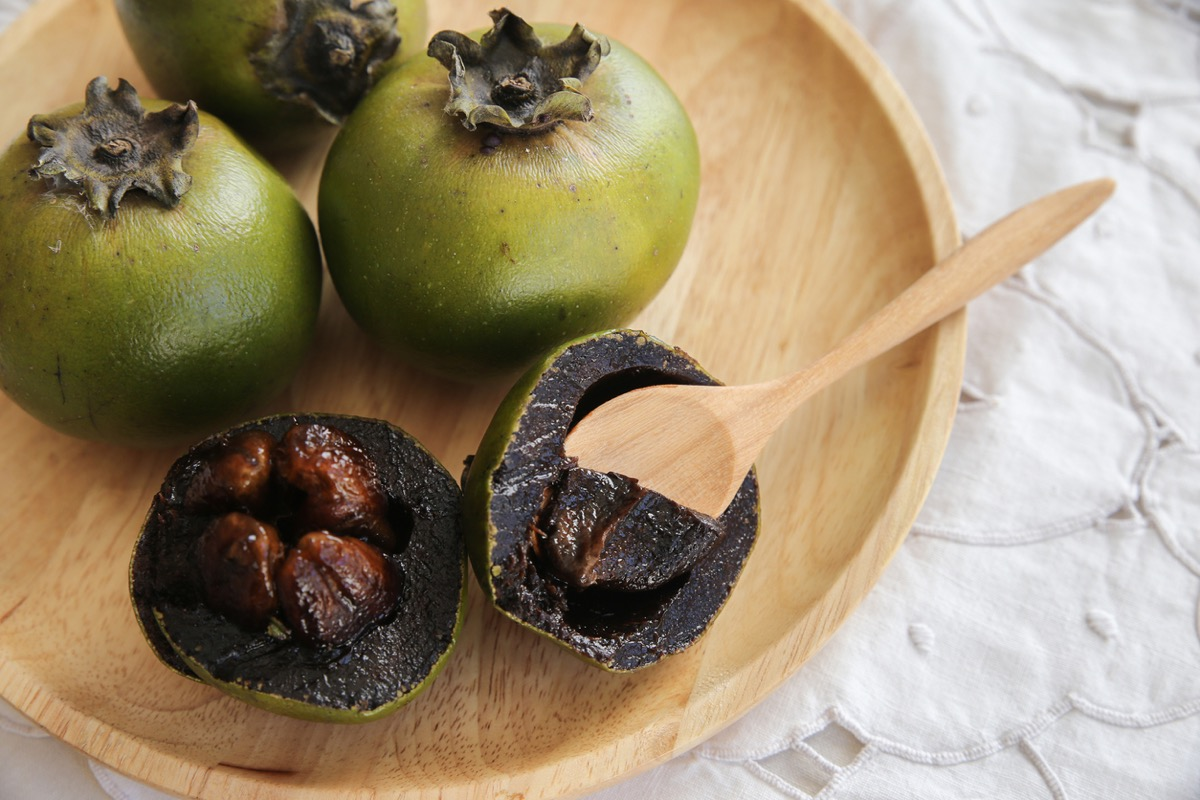 black sapote fruit with a wooden spoon in it