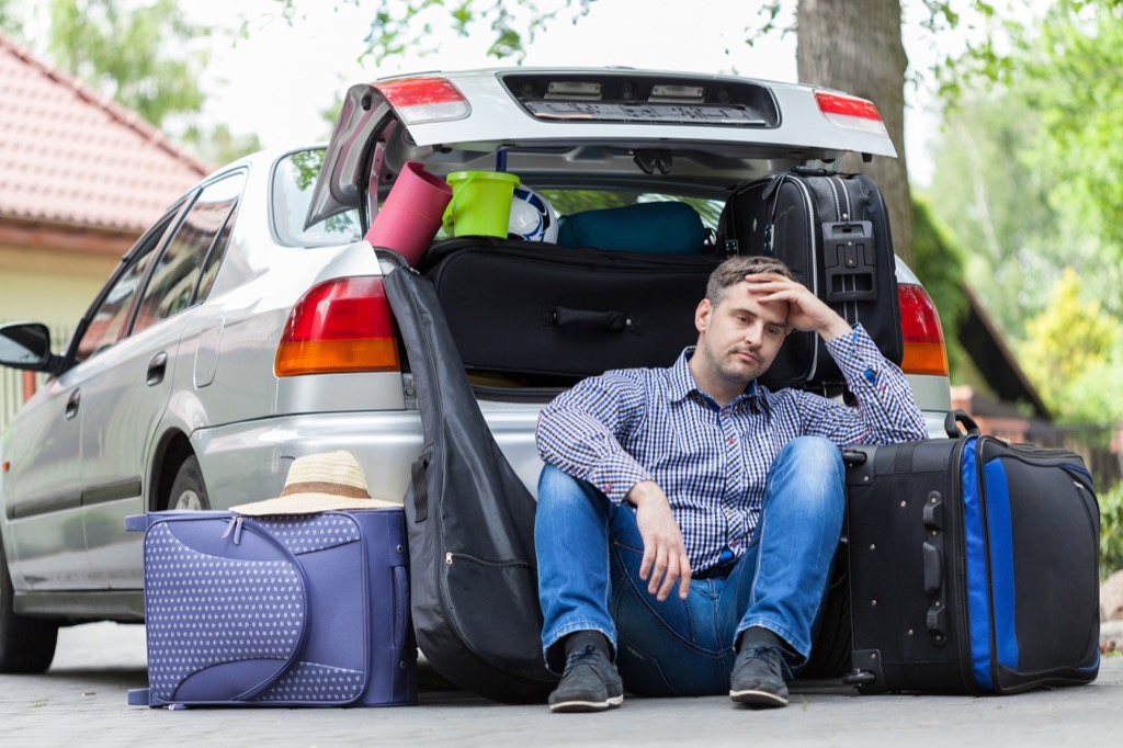 man with bags going into car