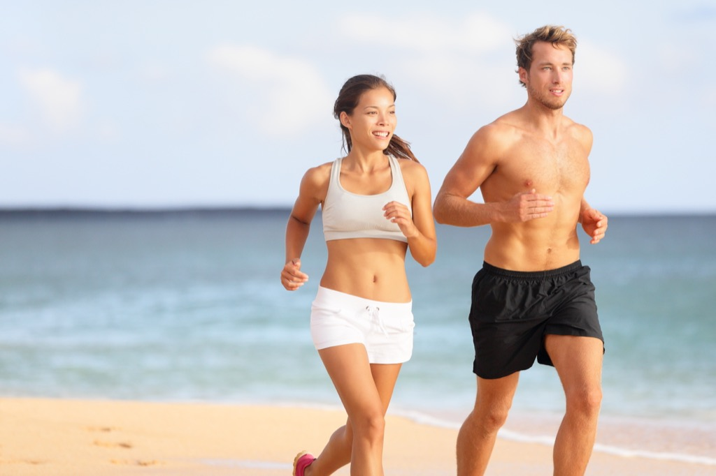 man and woman couple running at the beach man and woman exercising cardio workouts for men over 40