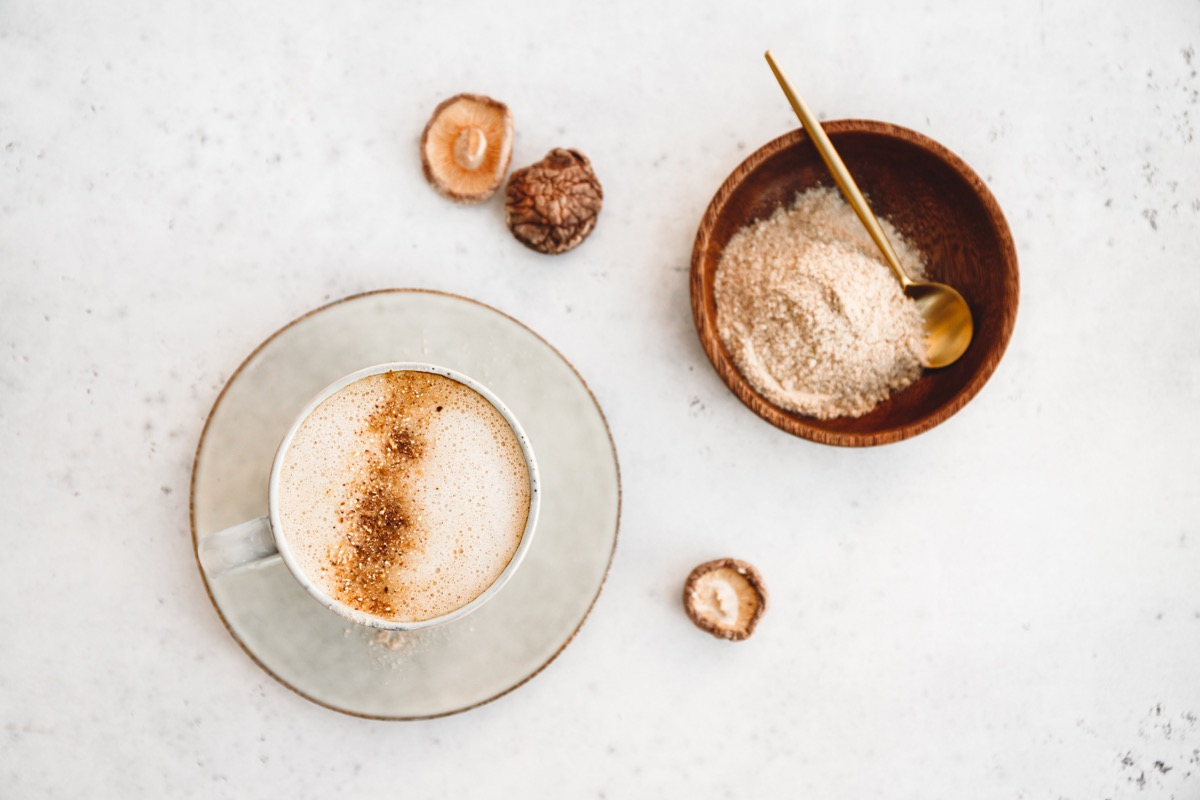 Top view of mushroom latte with shiitake powder and unsweetened coconut-almond blend milk. Healthy useful vegan drink, flat lay. (Top view of mushroom latte with shiitake powder and unsweetened coconut-almond blend milk. Healthy useful vegan drink, fl