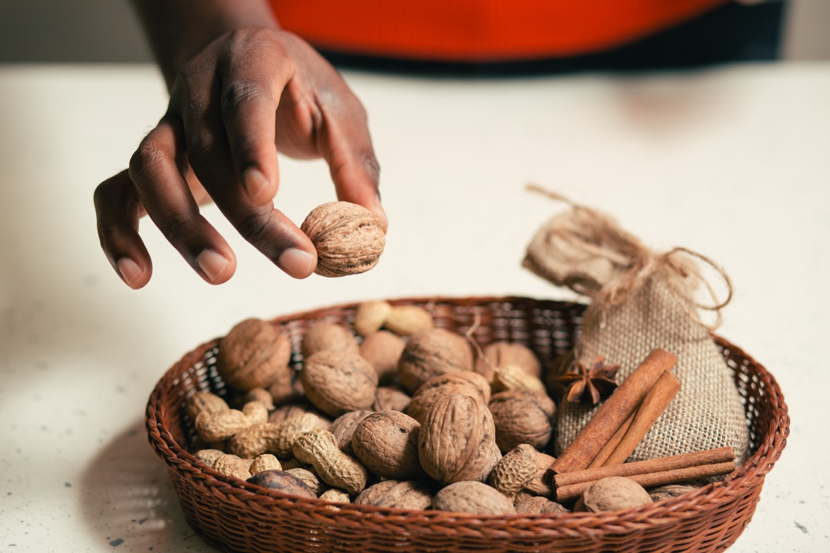 woman picking up a nut from a basket of nuts