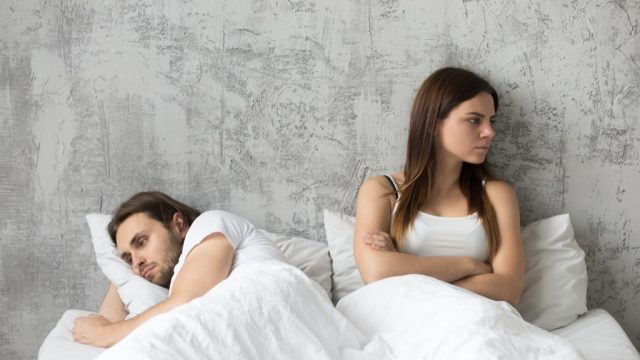 couple sitting in bed upset, stopped having sex