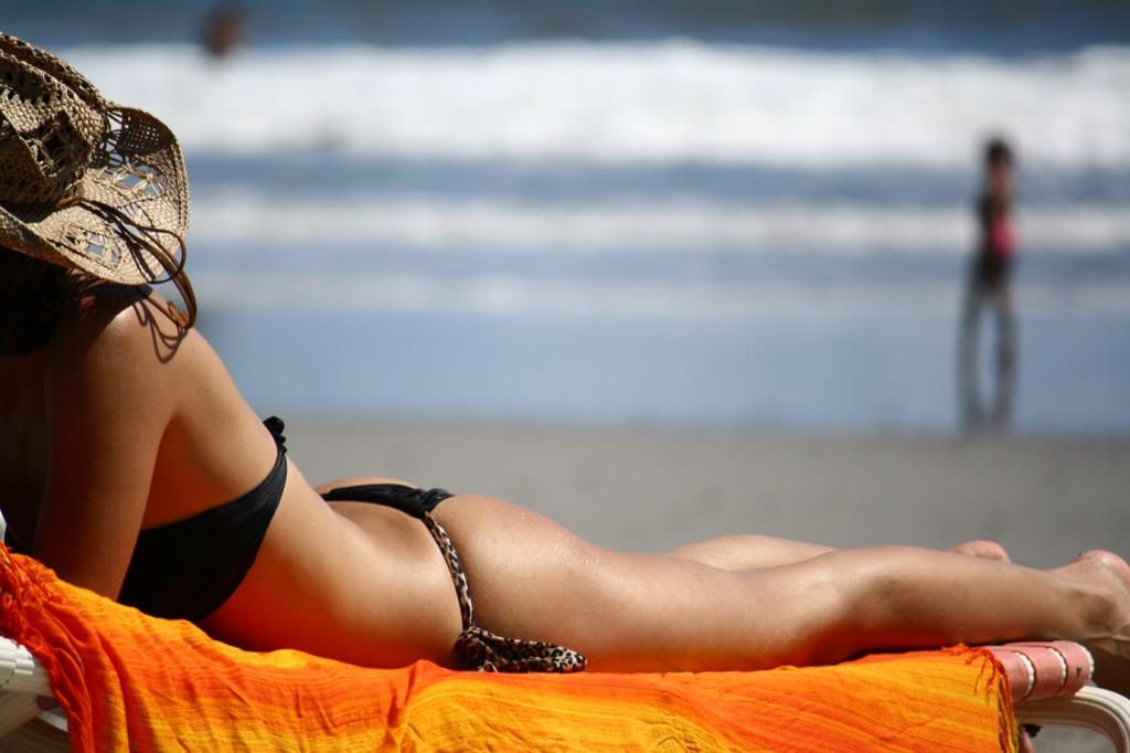 woman tanning worse skin