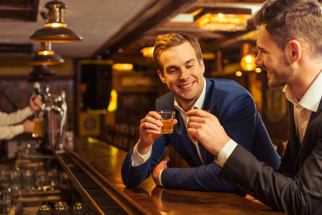 two businessmen drink at a bar