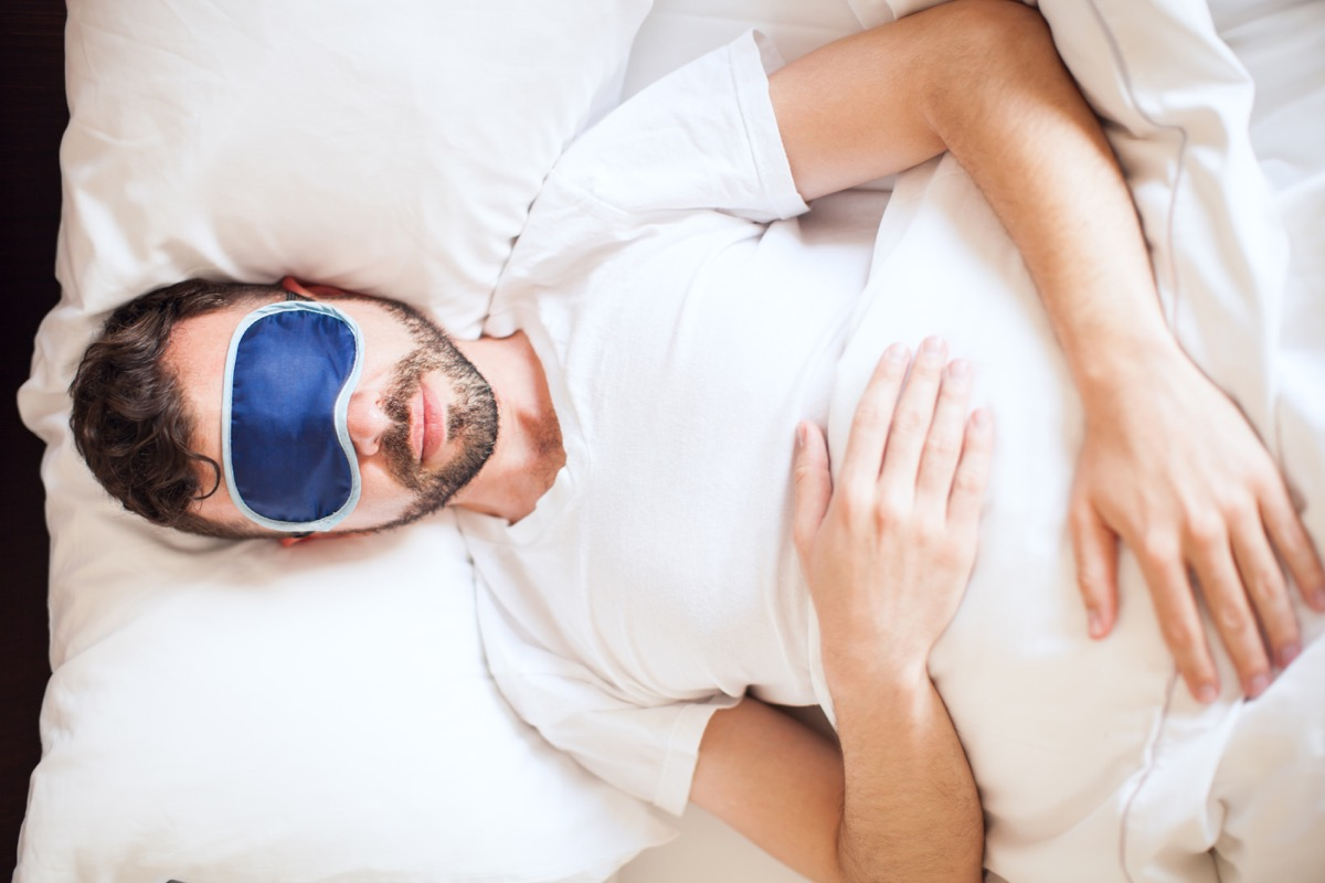 Top view of a young man wearing a sleep mask while getting some rest in his bedroom