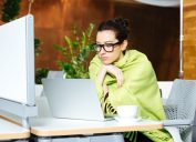shivering woman in office with blanket, signs your cold is serious