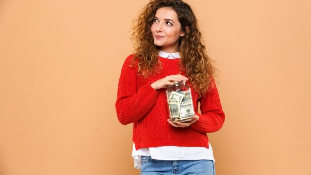 woman holds jar of money and wonders if it makes her an adult.