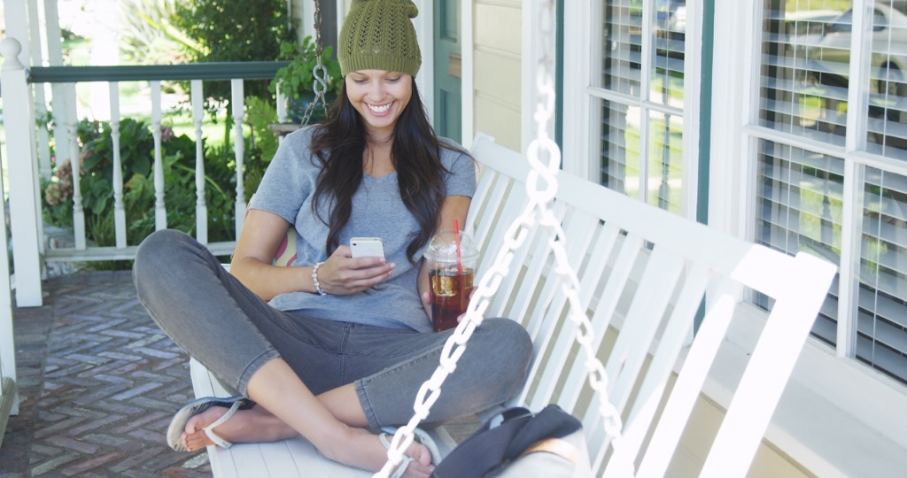 woman porch swing Boosting Your Home's Curb Appeal