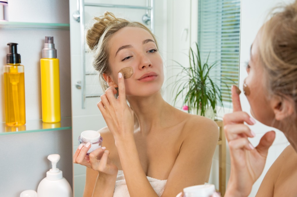 woman putting on makeup in mirror