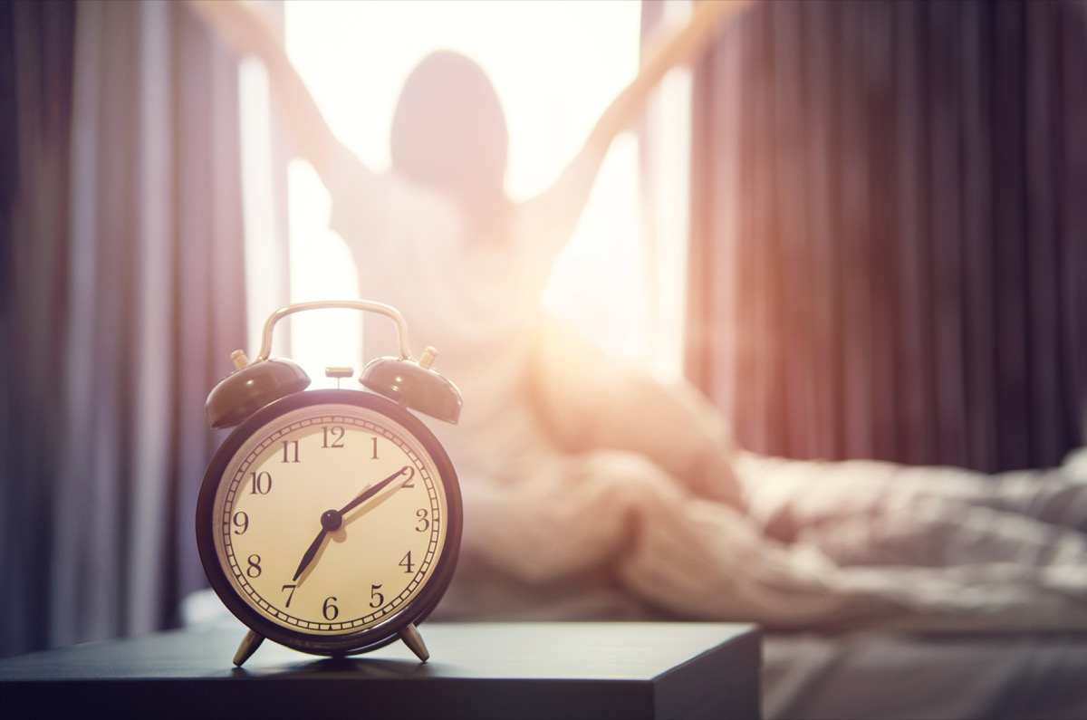 Closeup alarm clock having a good day with background happy woman stretching in bed after waking up, sunlight in morning.