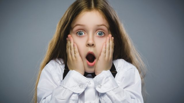 Amazed young girl in white shirt with hands on cheeks looking shocked, childlike wonder facts
