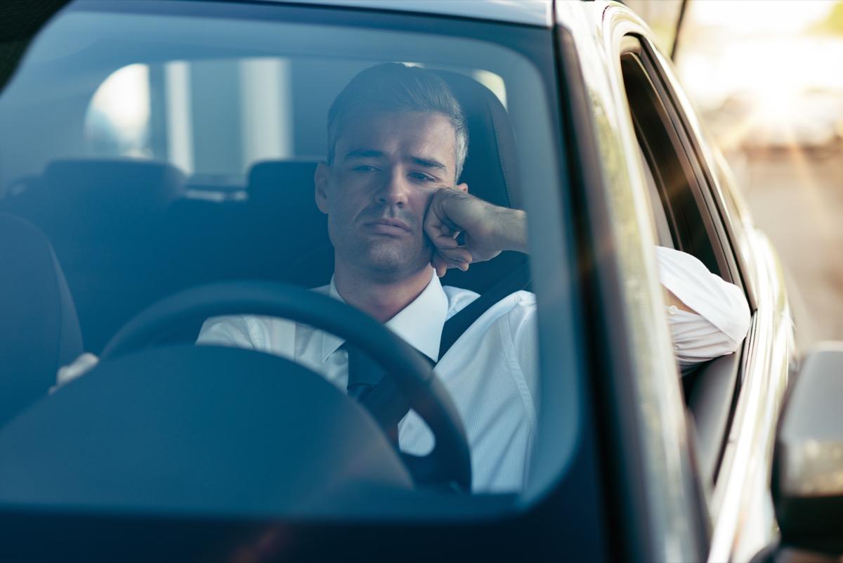 Man sitting in his car sad