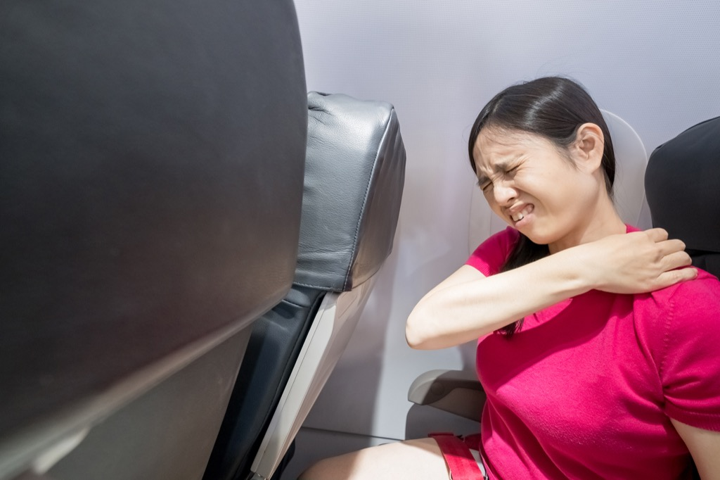 Woman has back pain on an airplane.