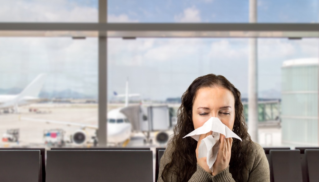 Woman sneezing at the airport {What to Do If You Have the Flu}