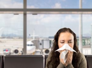 Woman sneezing at the airport.