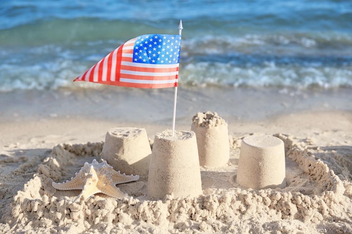 American flag in sand castle on beach