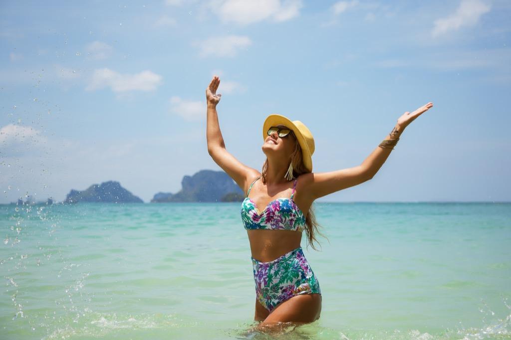 Woman in a high-waisted bikini at the beach.