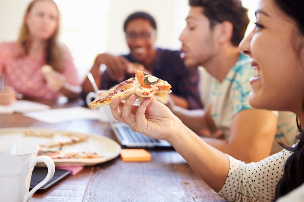 office workers eating pizza in a meeting