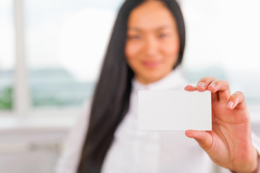 Businesswoman handing over a blank business card.