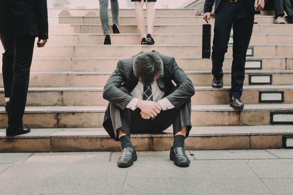 Businessman is a failure, sad on the steps