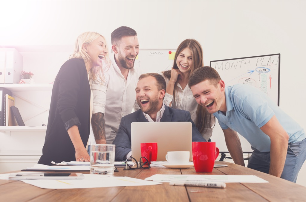 coworkers gathered around a laptop laughing