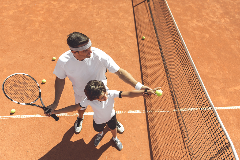 Dad Teaching Son How to Play Sports