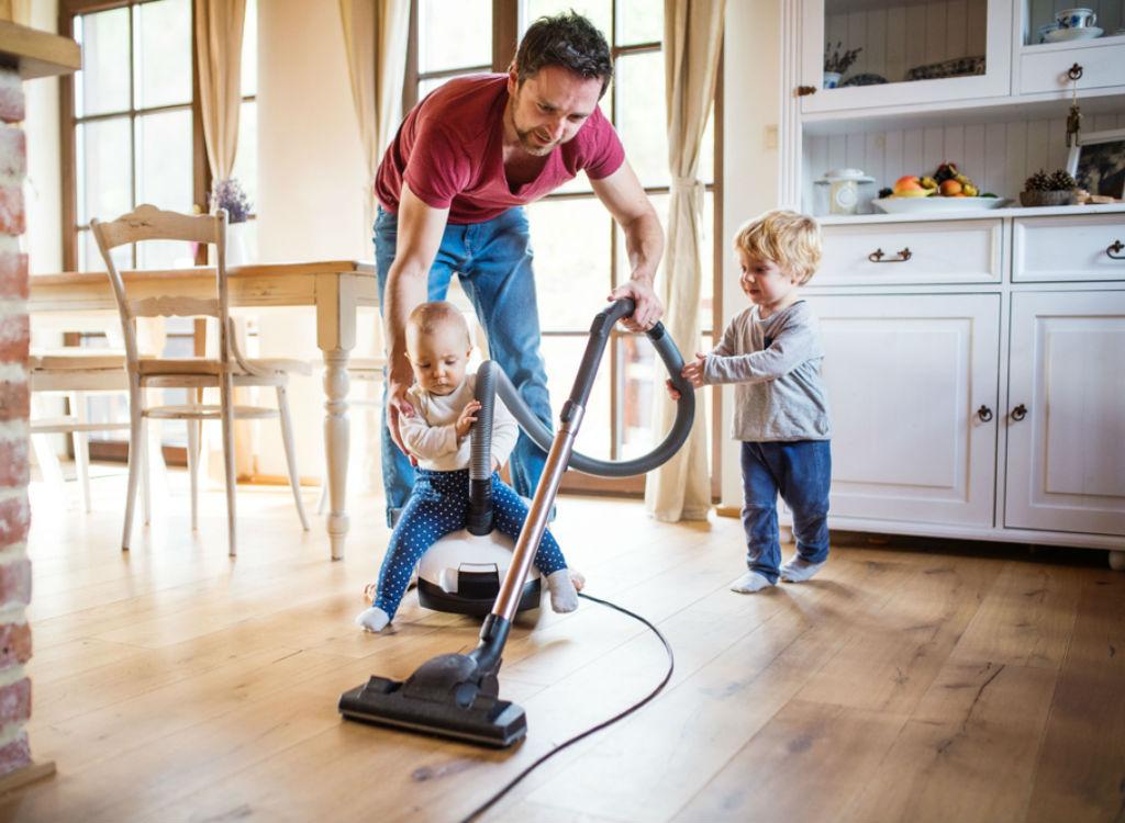 Man vacuuming floor with little kids