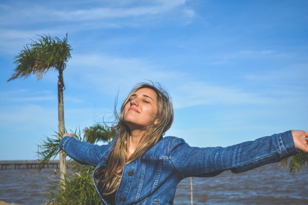 Woman taking a deep breath by the beach, relaxed