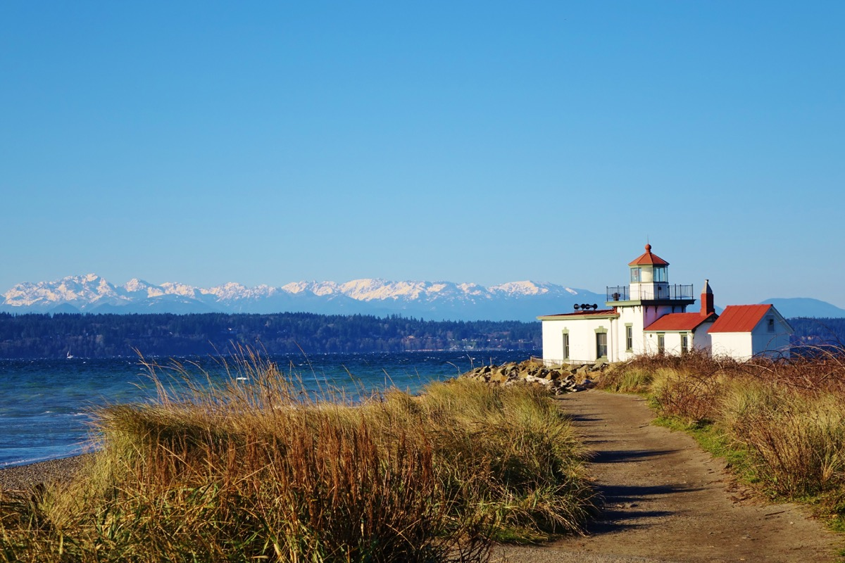 lighthouse against the water with mountains in the background