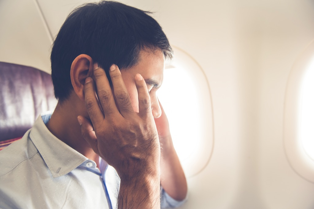 Man on an airplane holding his ears in pain.