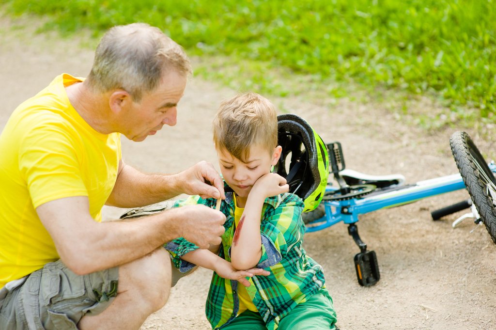 Dad putting bandaid on son Worst Things to Say to Kids